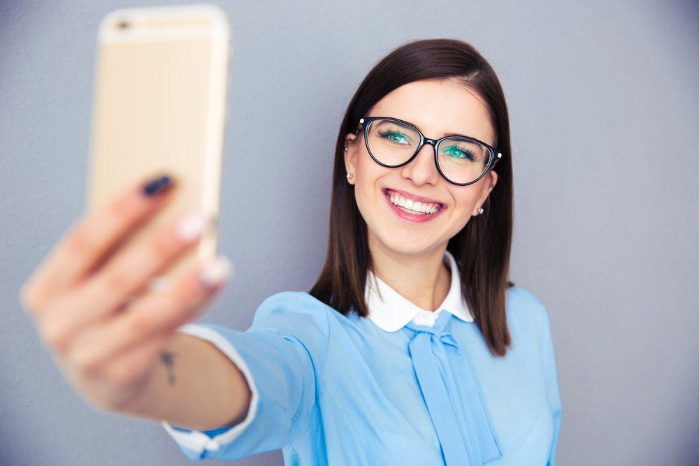 Smiling businesswoman taking selfie photo
