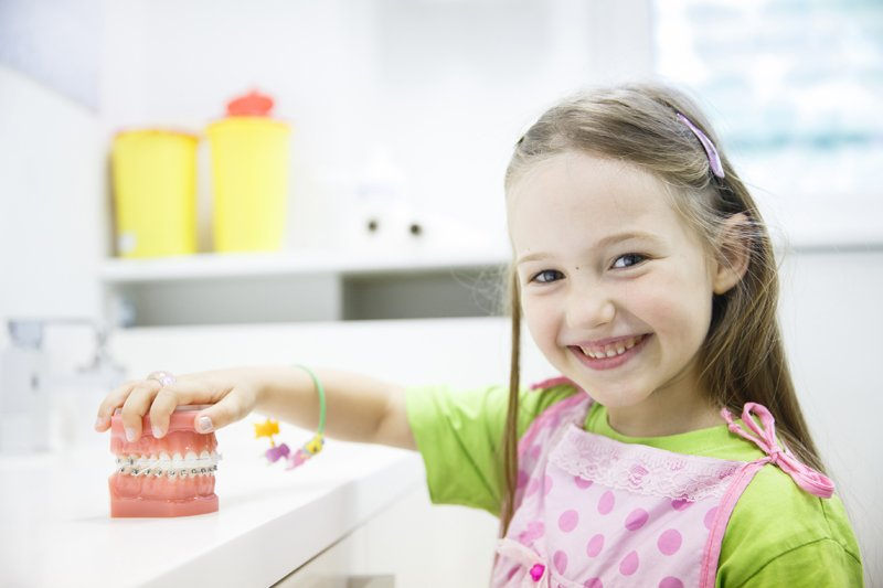 Girl holding model of human jaw with dental braces - Blackfoot orthodontics