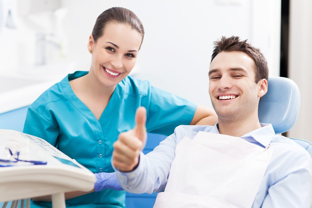 man giving thumbs up at dental office